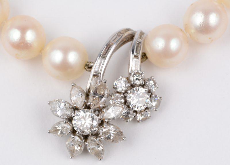 Een parelhalssnoer met 18 karaats wit gouden hanger en slot bezet met diamanten en baguettes met een gezamenlijk gewicht van ± 3 ct.