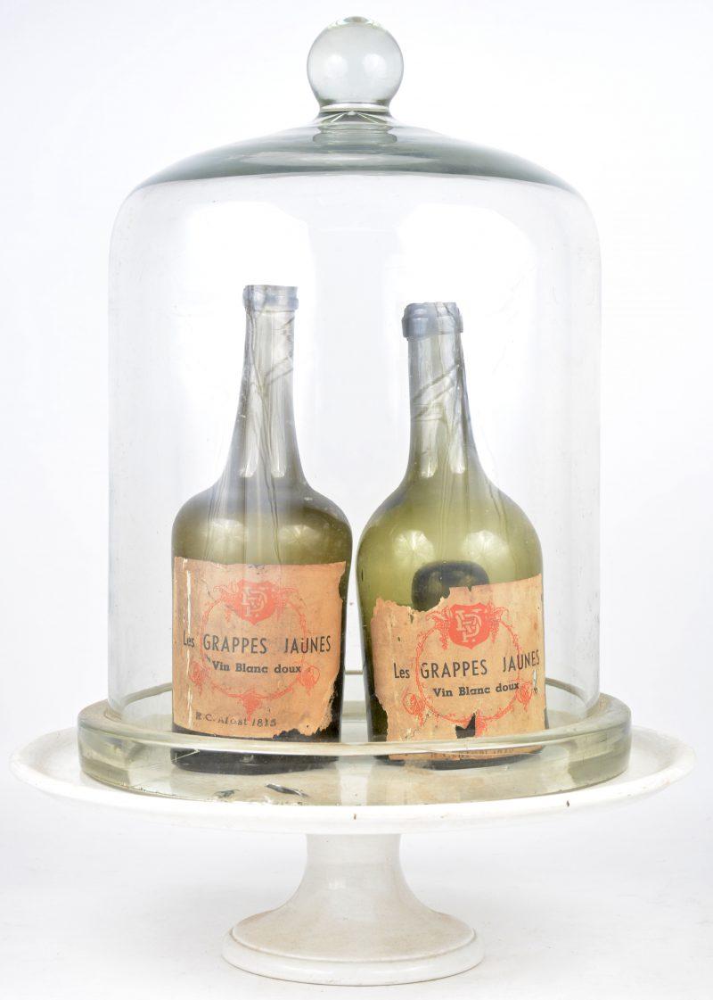 """Een oude glazen stolp op wit porseleinen voet. Eronder twee flessen van """"Les Grappes Jaunes"""" van 1815"""
