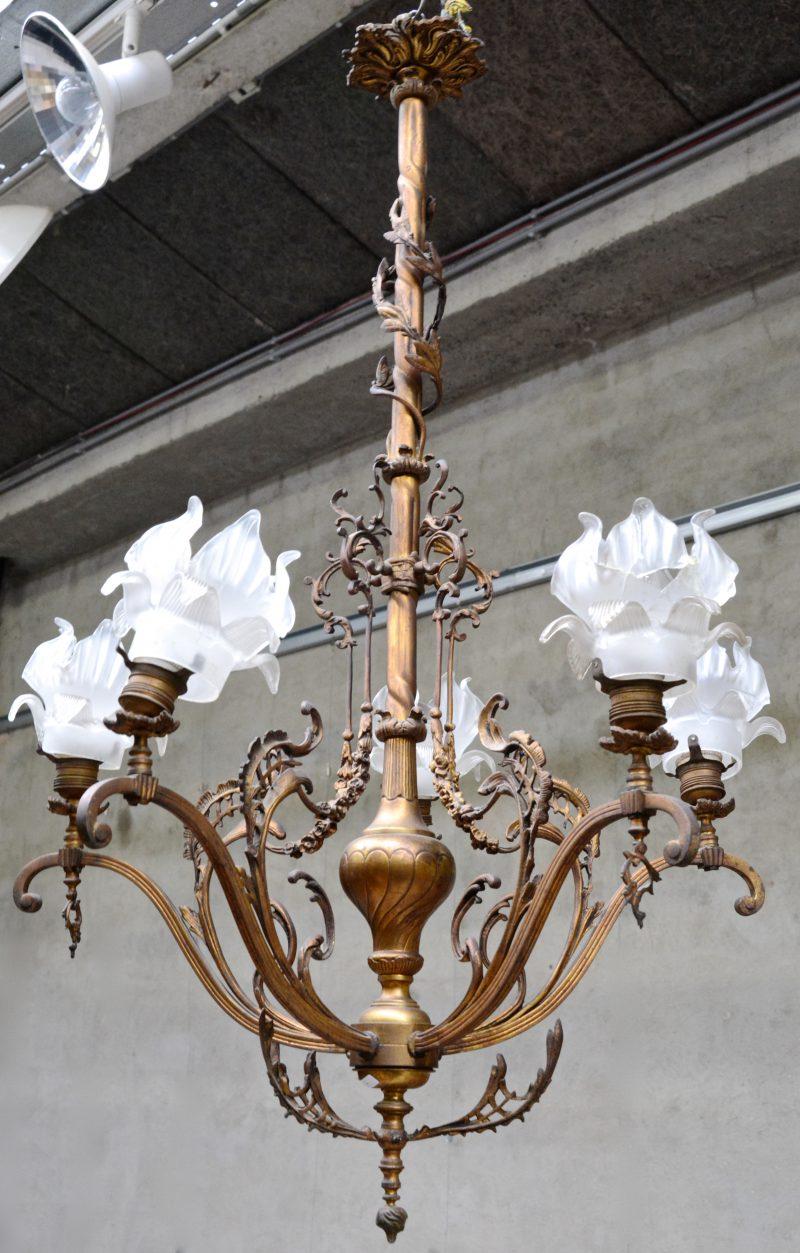 Een bronzen luchter met vier lichtpunten, getooid met bloemvormige glazen kapjes. Begin XXe eeuw.