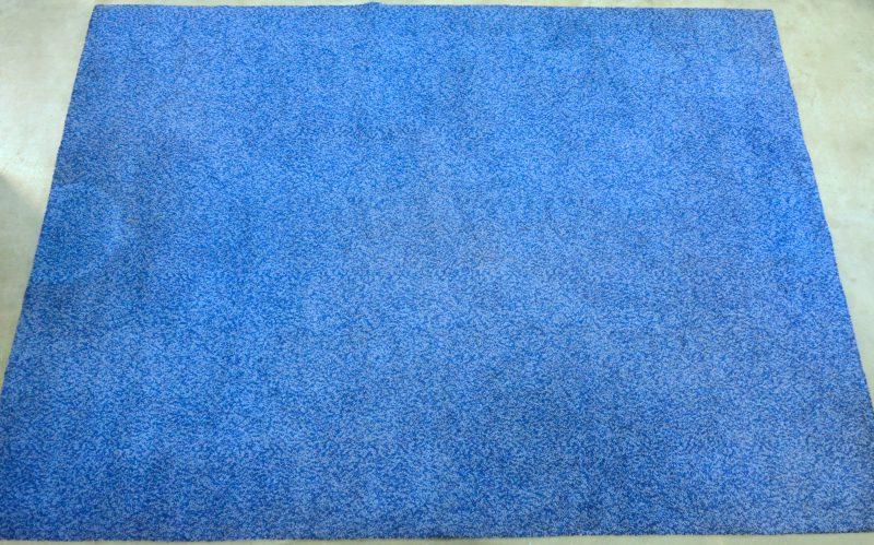 Een machinaal blauw wollen tapijt.