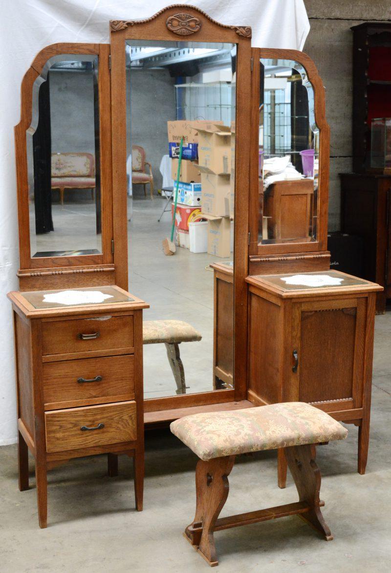 Een eikenhouten kaptafel met drie laden langs beide kanten met een glazen blad en met een spiegel met twee zijpanden. We voegen er klein zitbankje met kussen aan toe.
