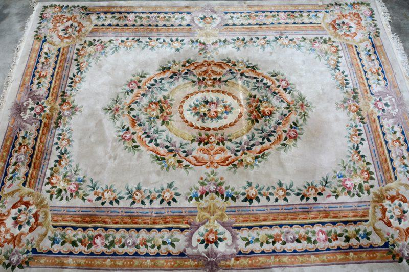Een Chinees wollen tapijt met bloemenmotieven. Twee beschadigingen van meubelpoten.