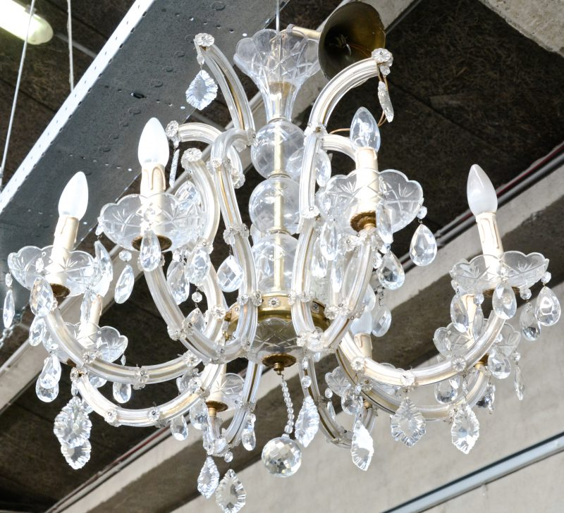 Een Marie-Thereseluchter met acht lichtarmen, versierd met kristallen pendeloques.