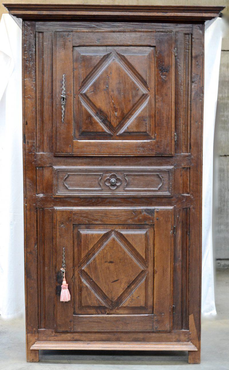 Een eikenhouten begijnenkast met twee boven elkaar geplaatste deuren waartussen een lade. Begin XIXde eeuw