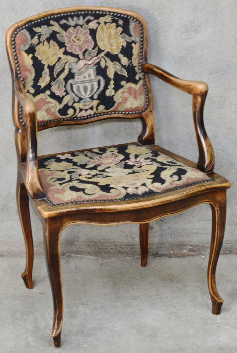 Een armstoeltje van gebeeldhouwd notenhout in Lodewijk XV-stijl, bekleed met naaldwerk.