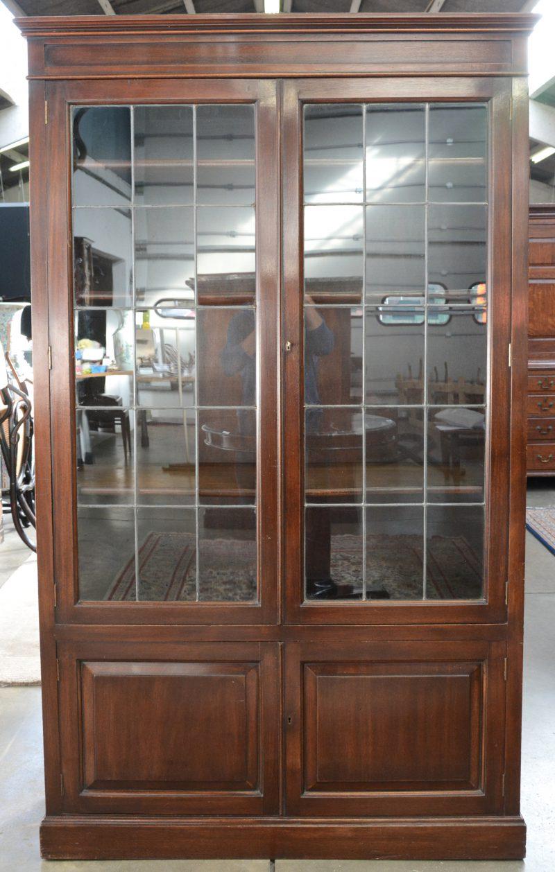 Een Engels bibliotheekkast met twee deuren met glas in lood boven twee kleinere paneeldeurtjes.
