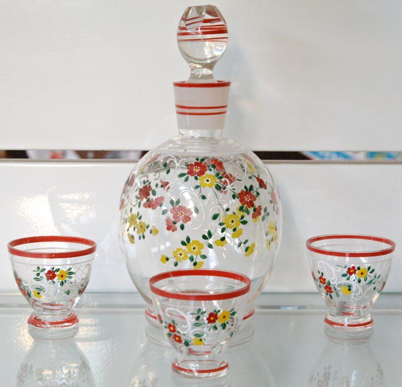 Een bol glazen karafje met drie bijpassende glaasjes met handgeschilderde decors. Omstreeks 1900.