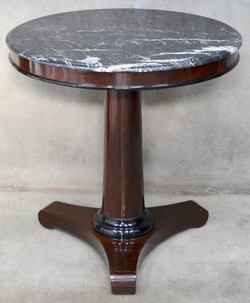 Een ronde notenhouten tafel in Empirestijl met een zwart marmeren blad.