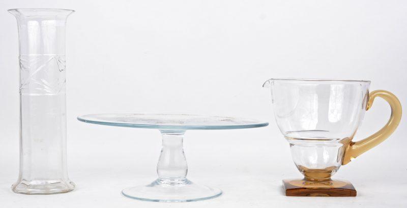 Een lot glaswerk, bestaande uit een kleurloze kokervaas, een taartenstaander en een schenkkan. De laatste met barst.