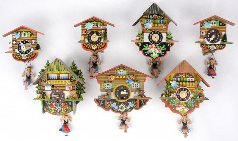 Een lot van zeven kleine koekoeksklokken van meerkleurig hout en kunststof met een slinger in de vorm van een schommelend meisje.