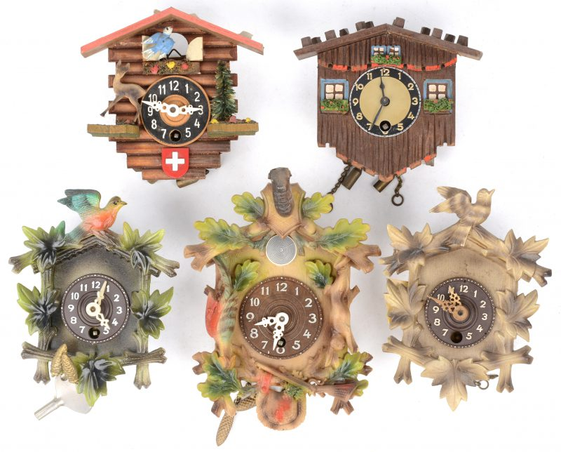 Een lot van vijf kleine koekoeksklokjes van hout en kunststof. Enkele slingertjes en sleuteltjes manco.