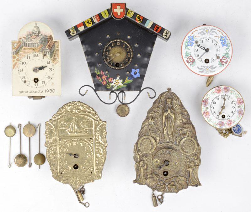 Een lot metalen miniatuurklokjes, waarbij een Zwitsers van smeedijzer, twee met bronzen wijzerplaat, twee met geëmailleerde wijzerplaat en met een afbeelding van de Sint Pietersbasiliek uit 1950. Enkele zonder slingertje.