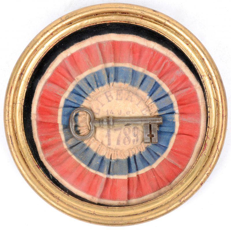 Een sleutel, afkomstig van de Bastille Saint-Antoine in rond kadertje, geschonken aan de stad Brugge. Met zegel.