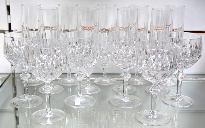 Een reeks glazen van geslepen kleurloos kristal, bestaande uit negen champagnefluiten en zes wijnglazen. Onderaan gemerkt. Eén fluit met schilfer.