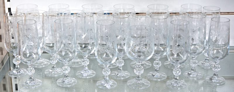 Een reeks glazen van geslepen kleurloos kristal met gegraveerde versieringen, bestaande uit twaalf champagnefluiten en twaalf wijnglazen.