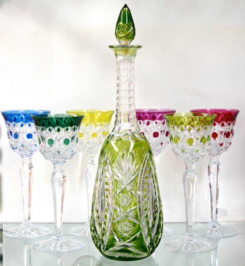 Een reeks van zes glazen van geslepen kristal in diverse kleuren. Gemerkt onderaan. We voegen er karaf in dezelfde stijl aan toe. Jaren '70.