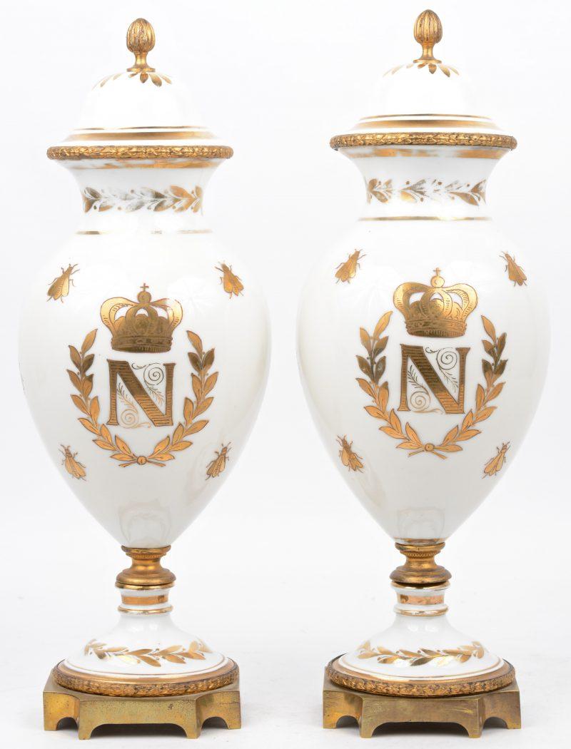 Een paar balustervormige dekselvazen van wit porselein, versierd met vergulde Napoleondecors en met messingen monturen. XIXe eeuw. Onderaan gemerkt.