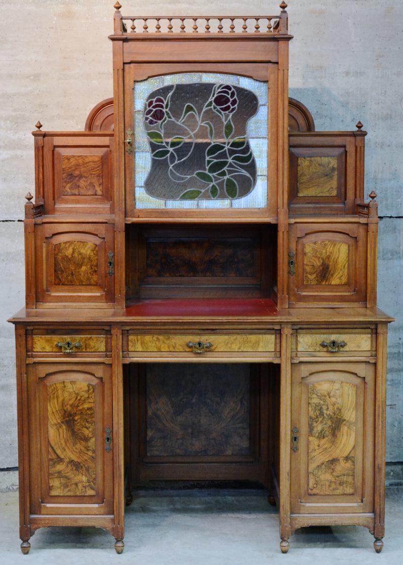 Een bureau van notenhoutfineer met opzet. Onderaan twee deuren en drie laden, bovenaan twee kleine paneeldeurtjes naast een grote deur met glas in lood. Belle epoque.