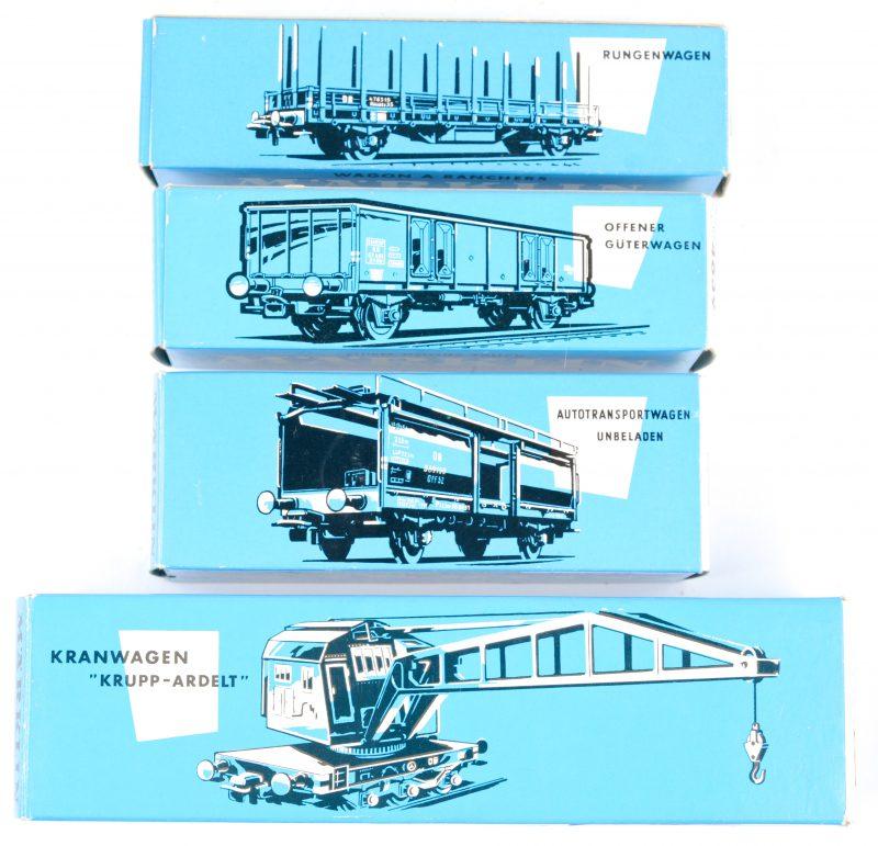 Vier goederenwagons voor spoortype Ho in originele doosjes: - Open wagon met steunpalen.- Spoorkraan 'Krupp-Adelt'.- Lege autotransportwagon.- Open goederenwagon.
