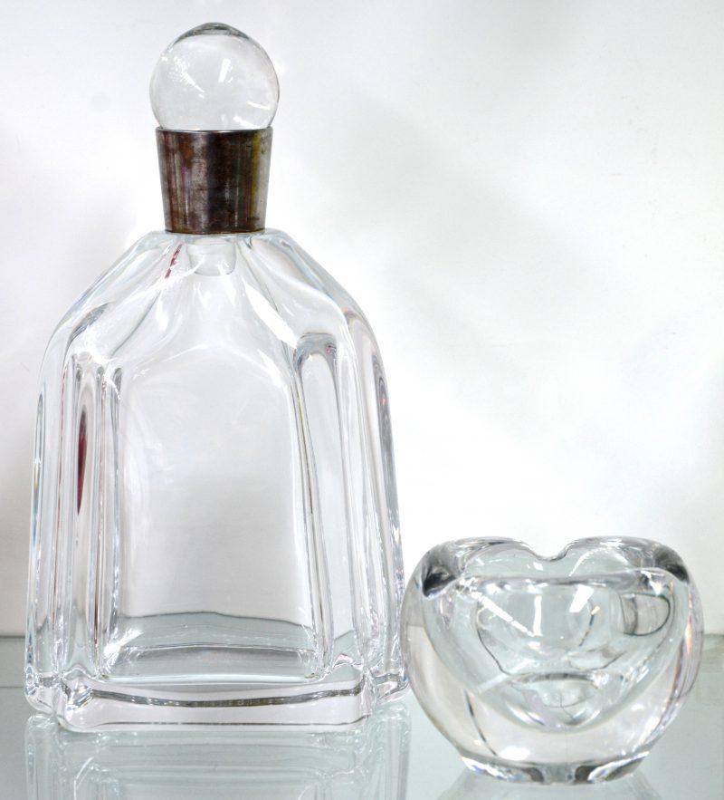 Een karaf van kleurloos kristal met witmetalen hals en een kleurloze asbak. Beide gemerkt.