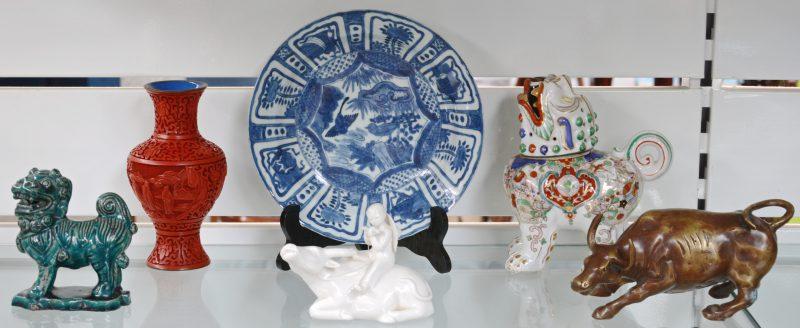 Een lot van zes stuks Chinoiserie, bestaande uit een diep bord met blauw-wit decor, een kind op een buffel van wit porselein, een fo-hond van groen aardewerk, een buffel van brons, een balustervaasje van rode lak en een porseleinen wierrookbrander in de vorm van een tempelleeuw.