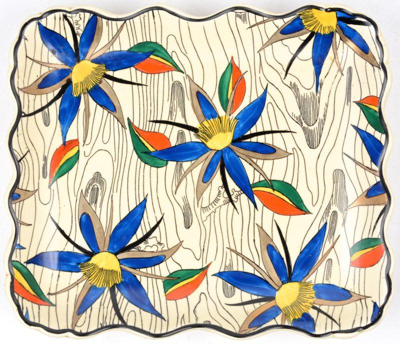 Een aardewerken sierschotel met gegolfde rand en met een meerkleurig bloemendecor. Onderaan gemerkt.