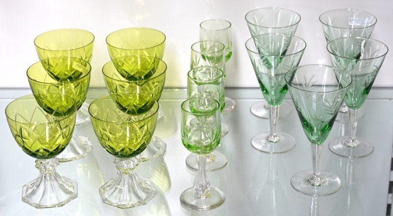 Een lot glazen, bestaande uit zes kelkglaasjes met gegraveerd decor, zes groene römerglazen met geslepen kleurloze voet en vier geslepen groene glaasjes op voet.