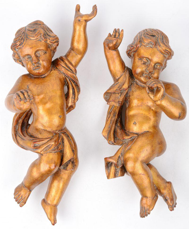 Twee wandversieringen van goudgepatineerd hout in de vorm van putti.