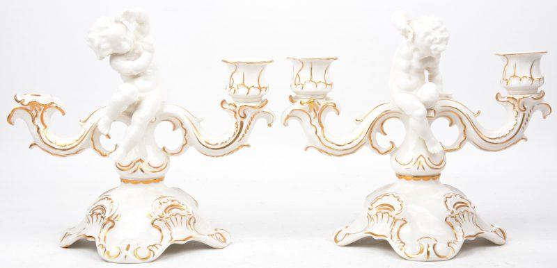 Een paar kandelaars van porselein versierd met personnages. Onderaan gemerkt.