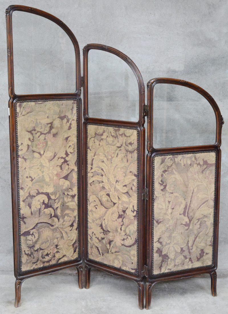 Een gebeeldhouwd notenhouten paravent met naaldwerk en bovenaan glazen ramen.