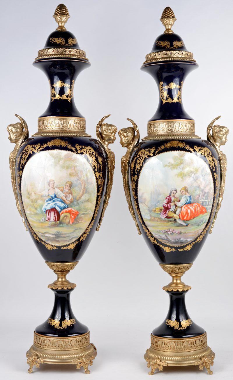 """Twee siervazen van kobaltblauw porselein in de stijl van Sèvres met bronzen voet en monturen en met meerkleurige decors van een koppel in een landschap in een cartouche, omringd met vergulde versieringen. Achteraan gemerkt """"A.C.F."""""""