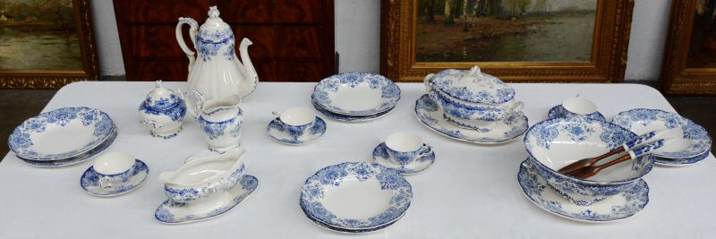Een aardewerken servies met blauw decor 'Dordrecht', bestaande uit 24 grote borden, twaalf kleine borden, 17 diepe borden, een vierdelig theestel met twaalf kopjes en schoteltjes, twee terrines, een sauskom en drie serveerschotels.