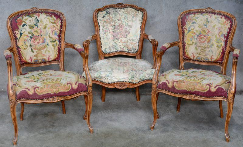 Drie armstoelen van gebeeldhouwd notenhout in Lodewijk XV-stijl, waarbij één licht afwijkend model.