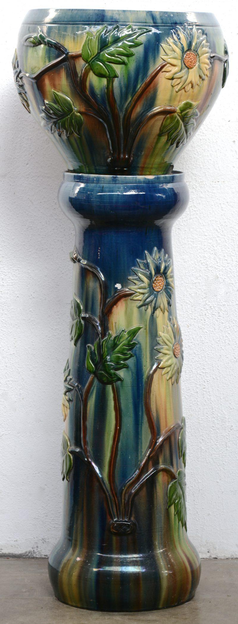 Een jardinière van Vlaams aardewerk met een bloemendecor in reliëf. Op piëdestal. Randschilfer aan de piëdestal.