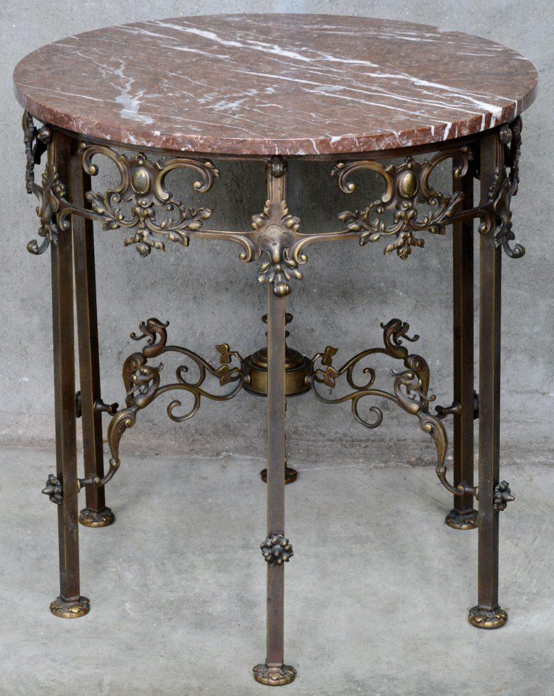 Een ronde koperen tafel op zes poten en met een rood marmeren blad.