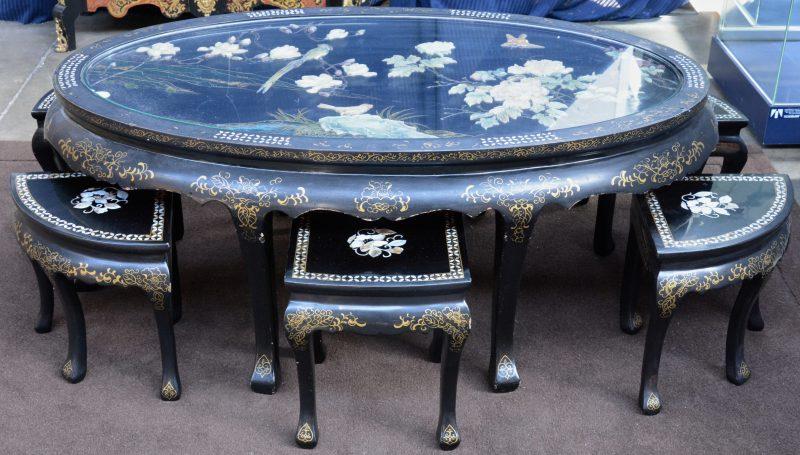 Een lage Chinese tafel van zwartgelakt hout met vergulde motieven. Het blad versierd met bloemen en vogels in pietra dura. Met zes stoeltjes.