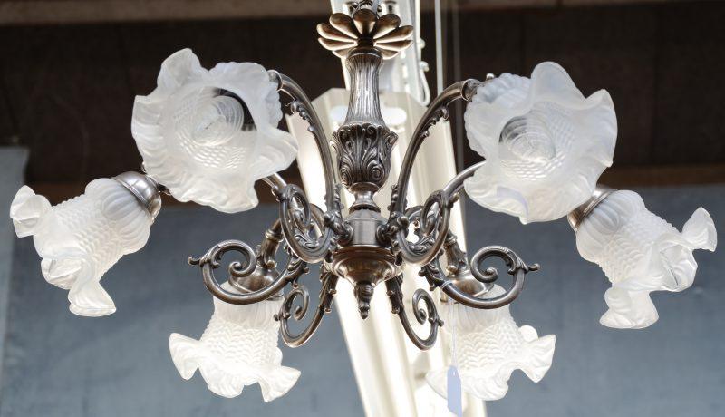 Een metalen luchtertje met drie lichtarmen en een centraal lichtpunt, eindigend in bloemvormige glazen kapjes.