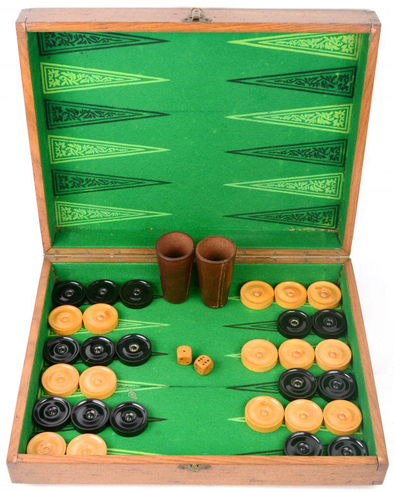 Een oude houten jacquetbak, compleet met dertig schijven, dobbelstenen en lederen bekertjes.