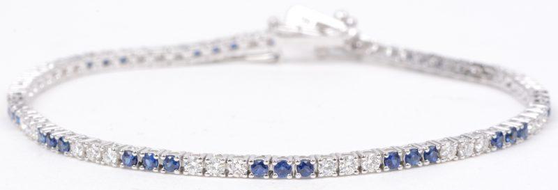 Een 18 karaats wit gouden schakelarmband bezet met diamanten met een gezamenlijk gewicht van ± 1,11 ct. en saffieren met een gezamenlijk gewicht van ± 1,37 ct.