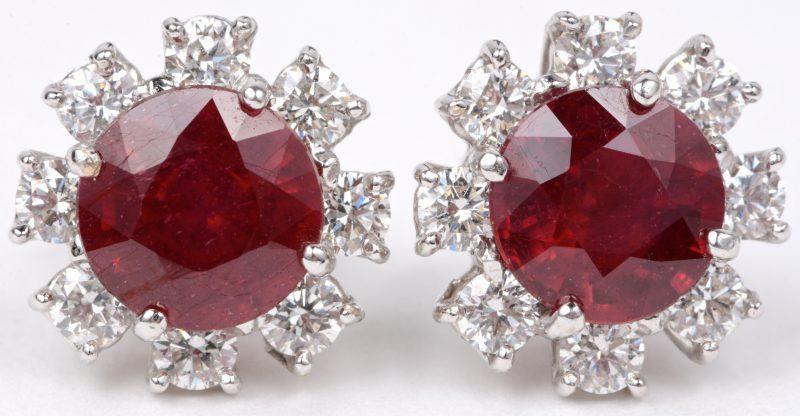 Een paar 18 karaats wit gouden oorbellen bezet met diamanten met een gezamenlijk gewicht van ± 1,16 ct. en robijnen met een gezamenlijk gewicht van ± 5 ct.