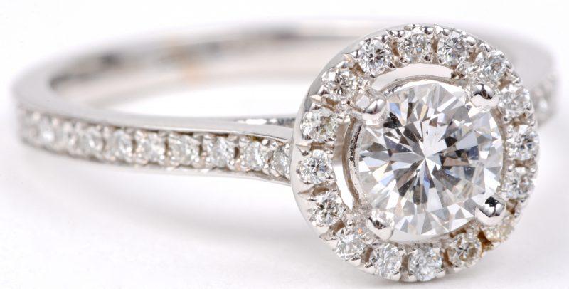 Een 18 karaats wit gouden ring bezet met een centrale diamant van ± 61 ct. en diamanten met een gezamenlijk gewicht van ± 0,29 ct.