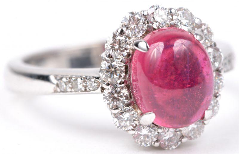 Een 18 karaats wit gouden ring bezet met een centrale robijn canochon van ± 2,12 ct. en diamanten met een gezamenlijk gewicht van ± 1,16 ct.