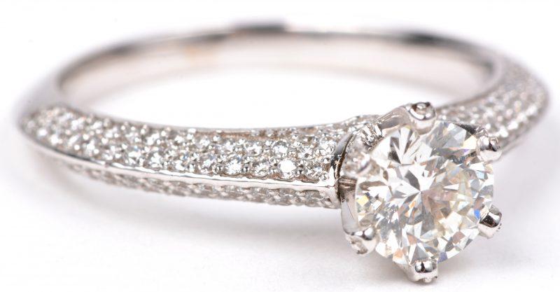 Een 18 karaats wit gouden ring bezet met een centrale diamant van ± 0,74  ct. en diamanten met een gezamenlijk gewicht van ± 0,56 ct.