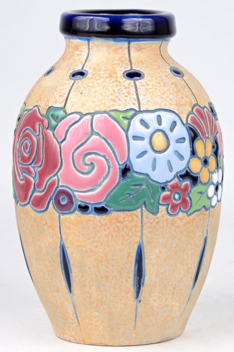 Een aardewerken vaasje met een meerkleurig bloemendecor in reliëf. Onderaan gemerkt. Barst in de rand.
