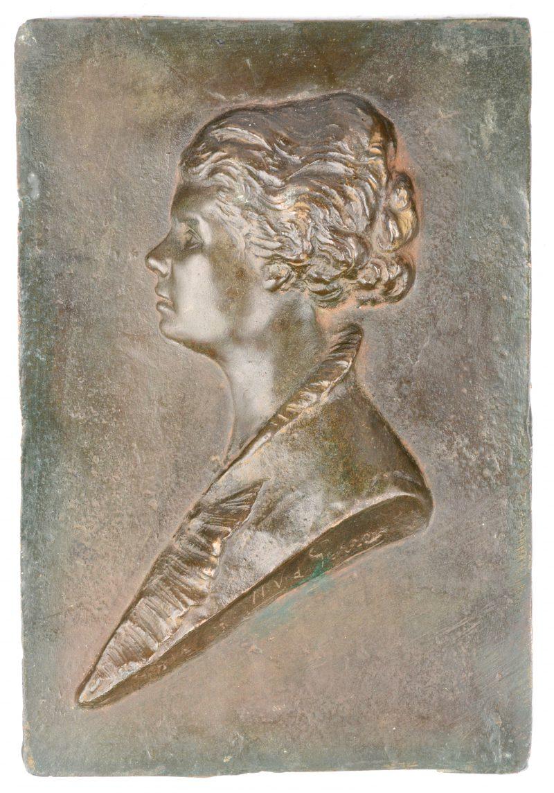 Een bronzen plaquette met een vrouwenprofiel in reliëf. Gesigneerd en gedateerd 1916.