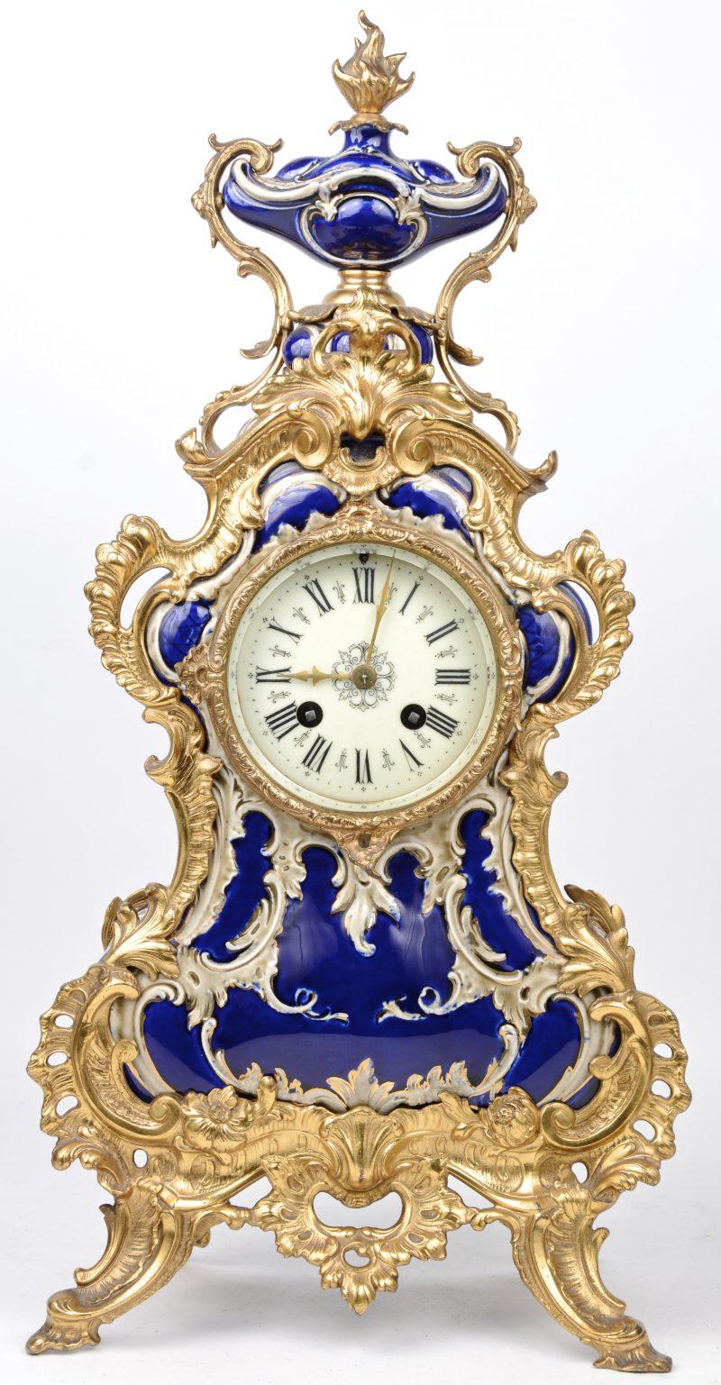 Een blauw aardewerken pendule met messingen frame.
