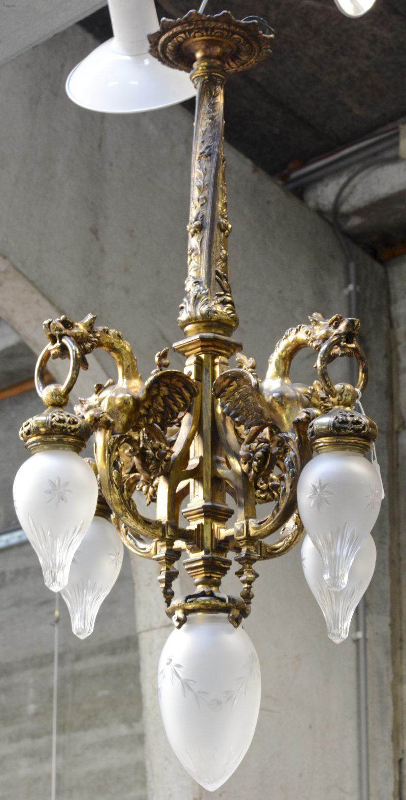 Een verguld bronzen luchter in eclectische stijl met vier lichtpunten, gedragen door vliegende draken.