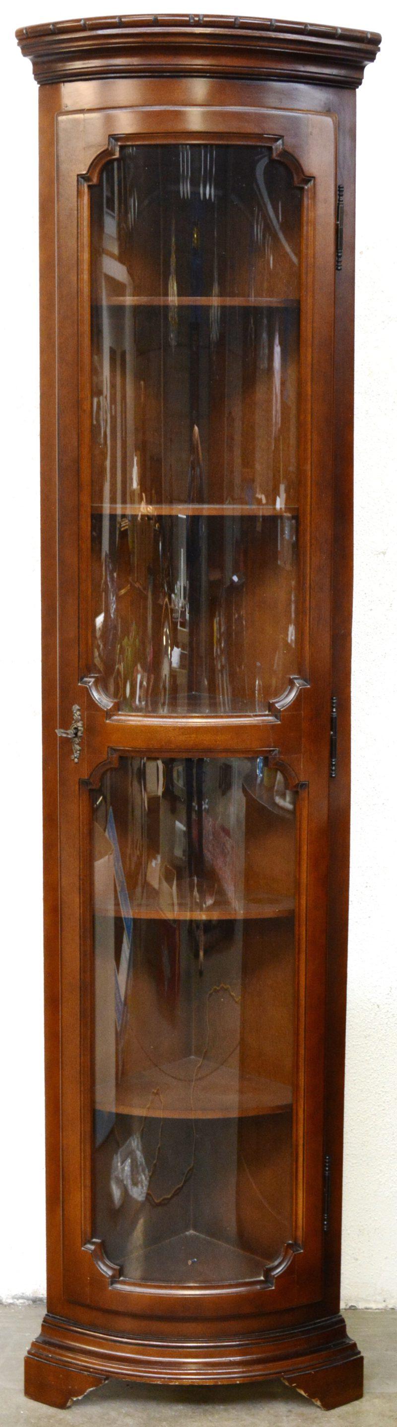 Een hoge hoekvitrine met één deur met bol glas.