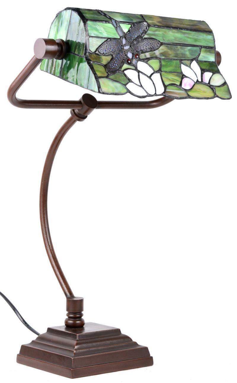 Een bureaulamp met een gekleurde kap in de geest van Tiffany met een libel in het decor.
