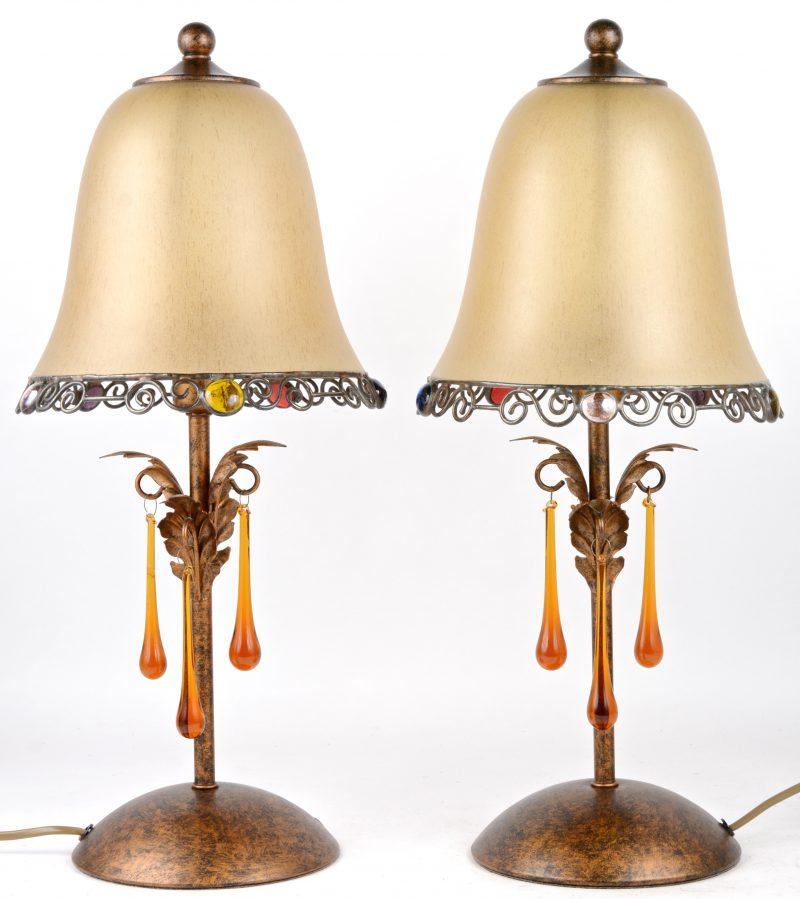 Een paar schemerlampen met glazen kappen, versierd met glazen parels en gekleurde pendeloques.